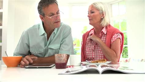 Older Couple Talking And Reading Magazine And Digital